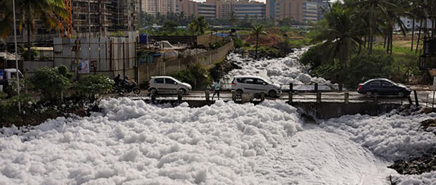 Bangalore, India was once known for its interconnected lake systems which provided a reliable source of water. As the city grew these lakes were encroached and the water became polluted day by day. The largest Bellandur Lake in Bangalore now carries huge volume of snowy froth which blocks the adjacent canals. This froth which would otherwise been a sight to behold stinks and on contact with skin causes irritation. Following a heavy rain the froth from the canal rises up and lands on the roads causing inconvenience to those travelling on two wheelers. This is a major concern with many such lakes in Bangalore which are getting polluted with harmful chemicals like nitrates, potassium, sulphates, etc. Although the residents have raised their concern by informing the local media for cleaning the lake, till date the Government has not taken adequate measures. The lake now emits intoxicating smell and blew froth all around whenever there is wind. Despite all such issues new residential complexes are still coming up. The affected area would be around 200 meters and if it too windy the froth flies even further entering the neighbouring houses. The people residing nearby the lake are suffering from several health issues.